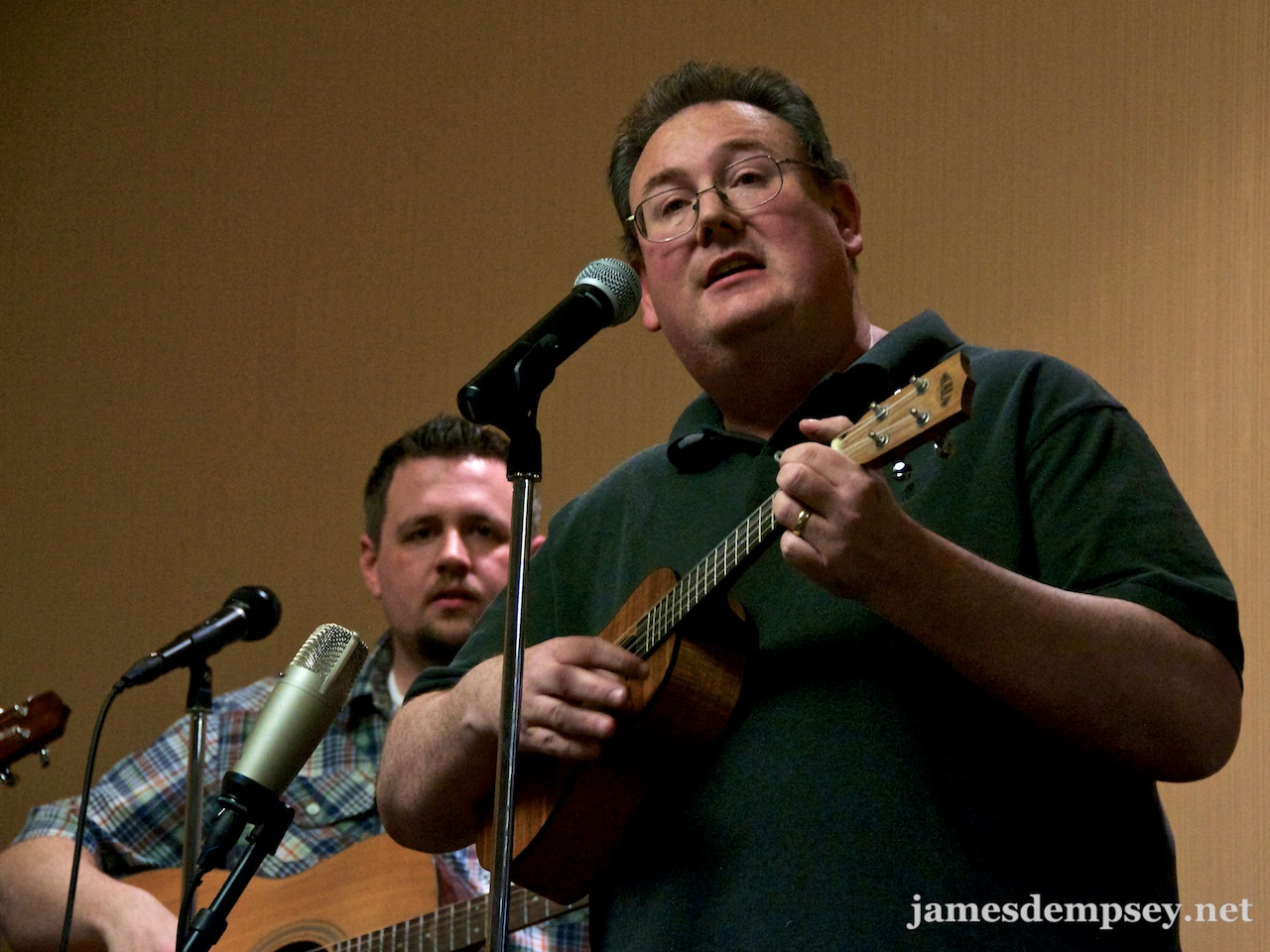 James Dempsey playing ukulele and singing and Ben Scheirman playing the guitar