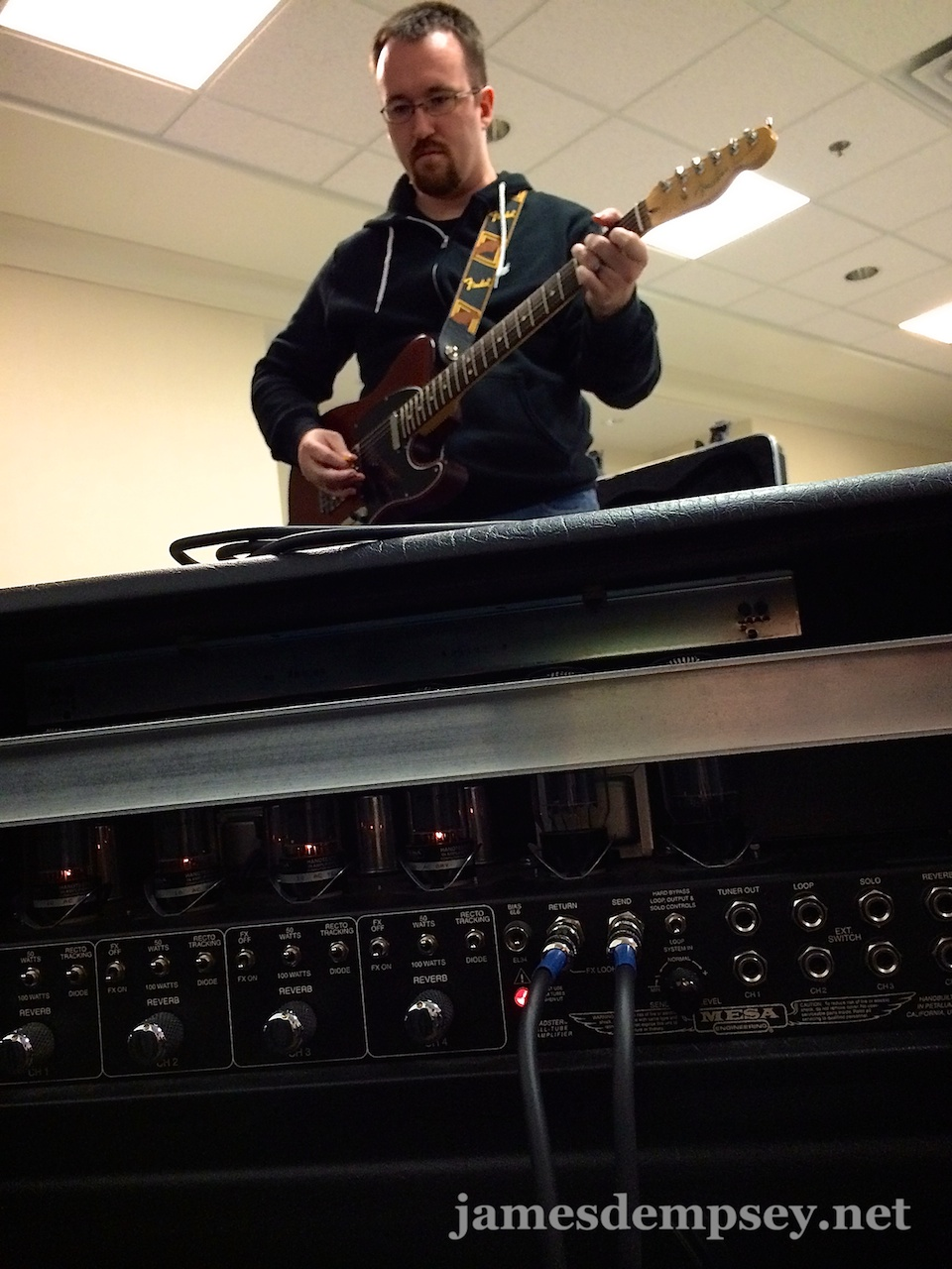 Brandon Alexander playing electric guitar in front of a big amplifier