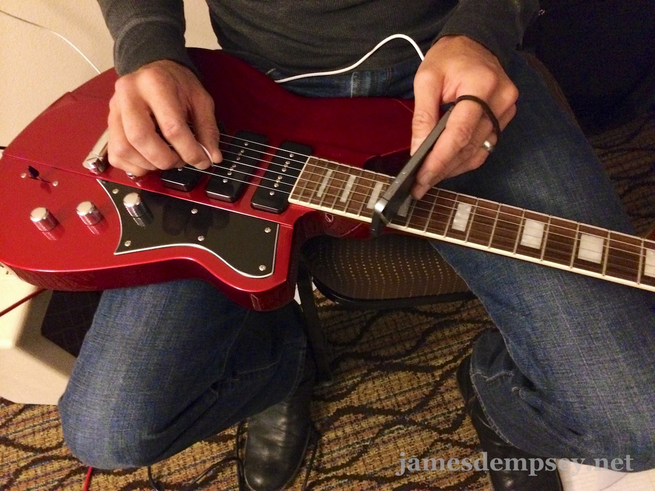 Closeup of using the edge of an iPhone as a guitar slide