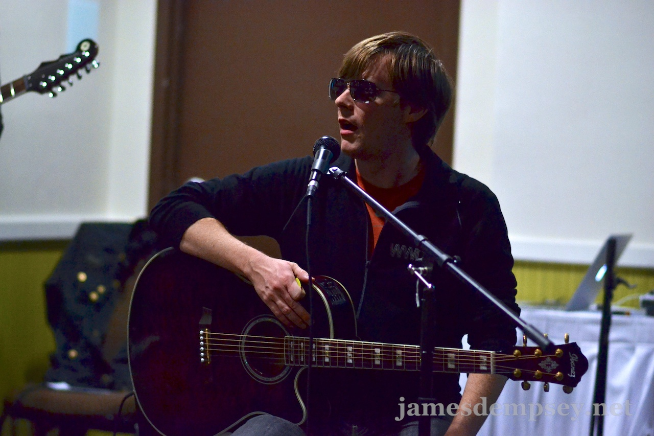 Jonathan Penn sitting with guitar, sunglasses on
