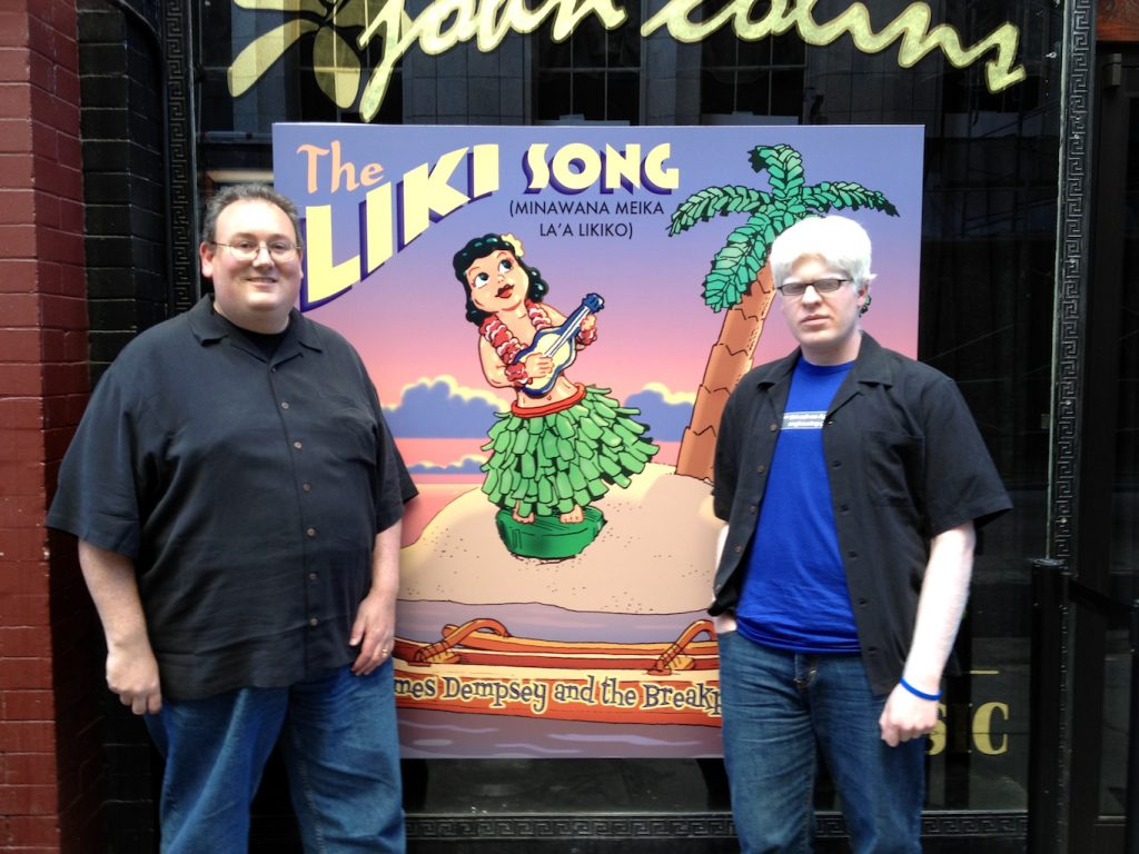 James Dempsey and Darren Minifie standing in front of The Liki Song poster, outside of John Colins bar in San Francisco